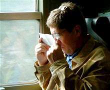 Man på tåg som tittar på ett papper på mycket nära håll