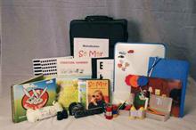 En uppackad väska med mycket saker, bland annat böcker, spel, kikare